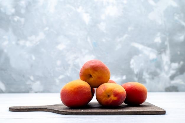 Uma vista frontal pêssegos frescos e suaves no fundo branco cor de frutas frescas
