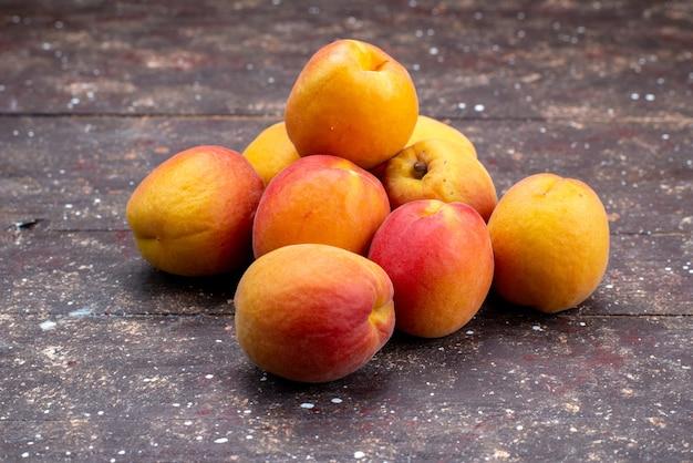 Uma vista frontal pêssegos maduros e suculentos na polpa de frutas da mesa de madeira do verão
