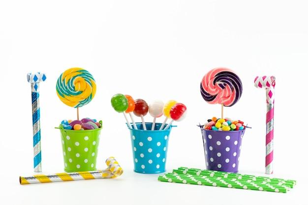 Uma vista frontal pirulitos e doces dentro de cestas em branco, cor açúcar doce