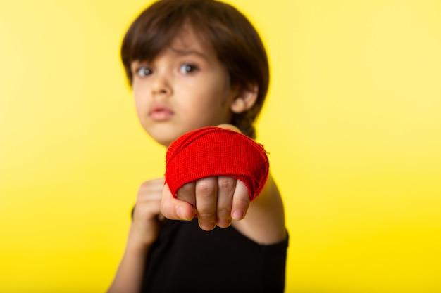 Uma vista frontal posando criança em camiseta preta e com uma mão amarrada com tecido vermelho na parede amarela