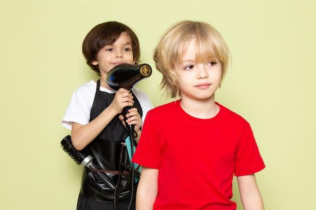 Uma vista frontal pouco cabeleireiro criança adorável trabalhando com penteado de meninos