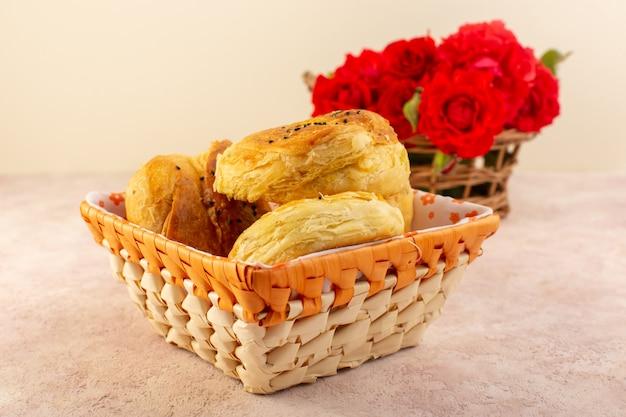 Uma vista frontal qogals assados, pães assados orientais, frescos e quentes dentro da caixa de pão junto com flores vermelhas na mesa e rosa