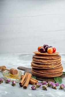 Uma vista frontal redonda de panquecas assadas e deliciosas com cerejas na mesa brilhante