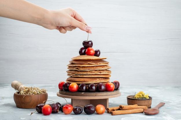 Uma vista frontal redonda de panquecas com cerejas e canela na fruta de bolo de fundo brilhante