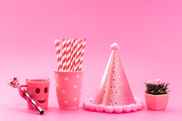 Uma vista frontal rosa, -branco, doces em forma de bastão com uma tampa de aniversário engraçada e plantinha em rosa, doce de cor fofura