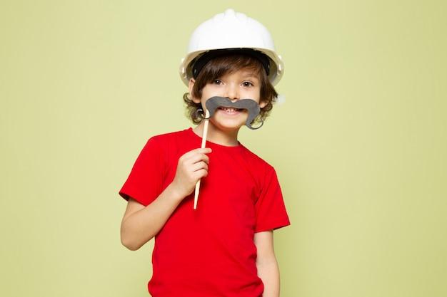 Uma vista frontal sorridente menino bonitinho na camiseta vermelha e capacete branco sobre o espaço colorido de pedra