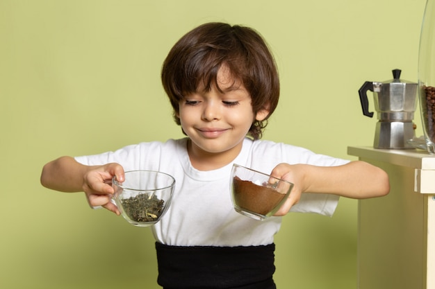 Uma vista frontal sorridente menino de camiseta branca, preparando o café na mesa de pedra colorida