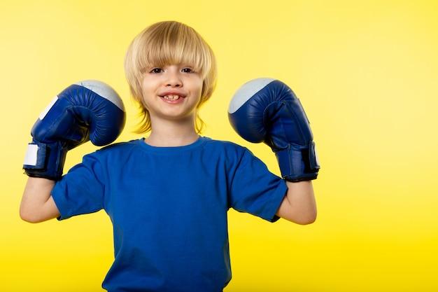 Uma vista frontal sorrindo loira flexionando com luvas de boxe azuis na parede amarela