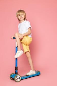 Uma vista frontal, sorrindo, loiro, menino, em, branca, t-shirt, montando scooter, ligado, a, espaço rosa