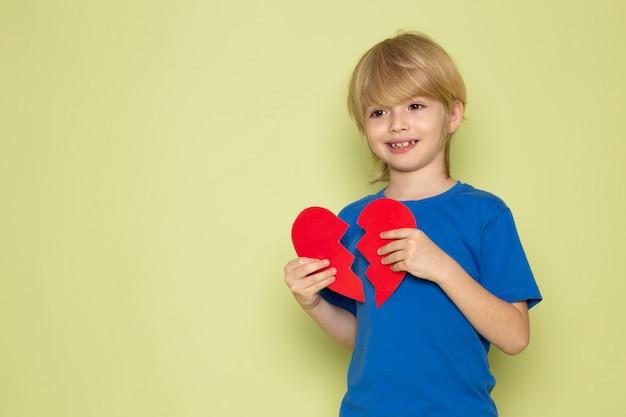 Uma vista frontal, sorrindo, loiro, menino, em, t-shirt azul, segurando, rasgado, coração, forma, ligado, a, cor pedra, backgorund