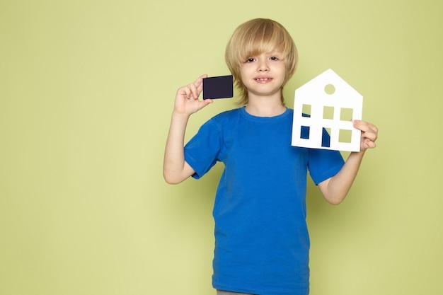 Uma vista frontal, sorrindo, loiro, menino, segurando, cartão, e, casa, dado forma, papel, em, t-shirt azul, ligado, a, pedra, espaço colorido
