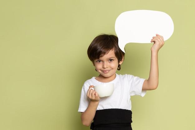 Uma vista frontal, sorrindo, menino criança, em, t-shirt branca, segurando, branca, sinal, ligado, a, pedra, espaço colorido