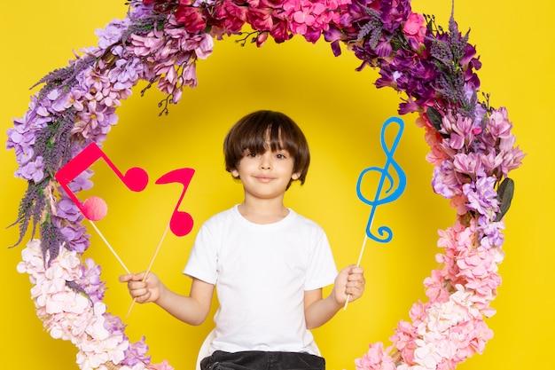 Uma vista frontal, sorrindo, menino, segurando notas, ligado, a, amarela, chão