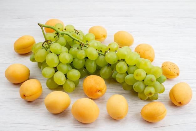 Uma vista frontal uvas verdes frescas com damascos na mesa branca frutas cor verde verão
