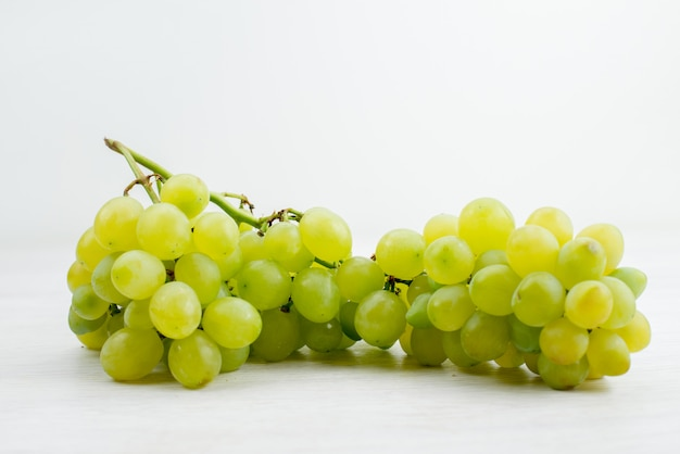 Uma vista frontal uvas verdes frescas suculentas e azedas na mesa branca vitamina cor de frutas verão