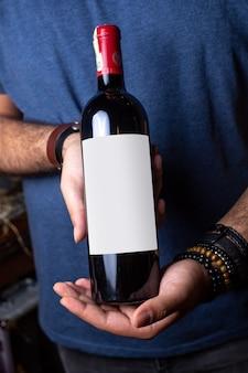 Uma vista frontal vinho tinto jovem segurando uma garrafa de vinho tinto com tampa vermelha álcool adega bebida