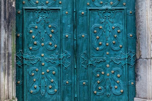 Uma vista incrível de uma antiga porta de metal turquesa da catedral católica com ornamentos
