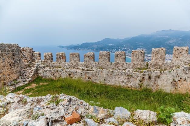 Uma vista incrível de uma fortaleza medieval no sul da cidade turca de alanya. uma parede antiga