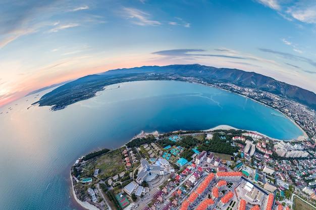 Uma vista panorâmica da baía de gelendzhik ao pôr do sol. a cidade turística está localizada na costa de uma bela baía marítima. as montanhas do cáucaso.