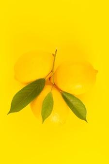 Uma vista superior amarelo limão fresco fresco maduro com folhas verdes, isoladas no fundo amarelo cor de frutas cítricas