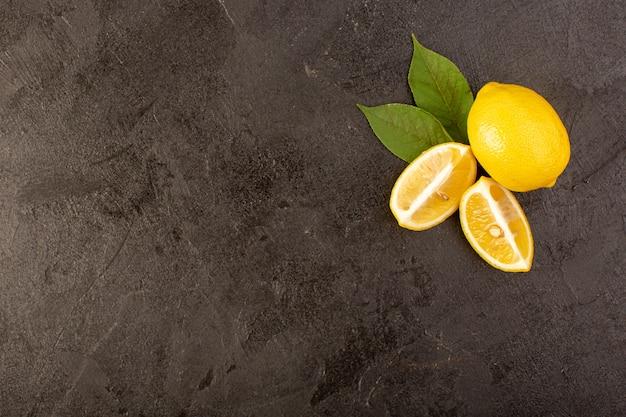 Uma vista superior amarelo limão fresco maduro e suculento inteiro e fatiado com folhas verdes sobre o fundo escuro frutas cítricas cor