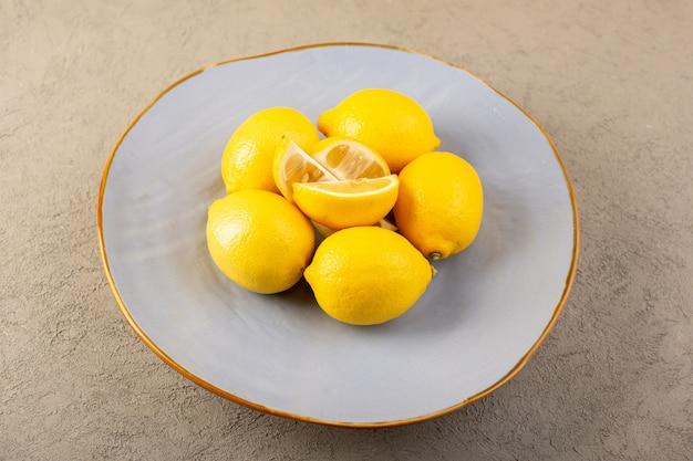 Uma vista superior amarelo limões frescos maduros e suculentos inteiros e cortados dentro da placa azul sobre o fundo cinza frutas cítricas cor