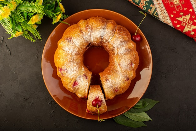 Uma vista superior assada de bolo de frutas delicioso redondo com cerejas vermelhas dentro e açúcar em pó dentro de um prato redondo marrom escuro
