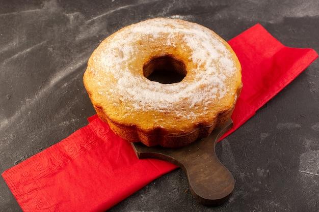 Uma vista superior assada em um bolo redondo com açúcar em pó na mesa de madeira