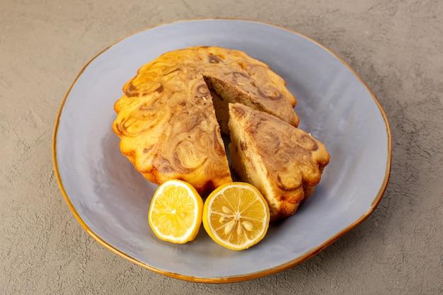 Uma vista superior bolo doce delicioso bolo de chocolate delicioso cortado dentro da placa azul junto com fatias de limão no fundo cinza assar biscoito de chá de açúcar