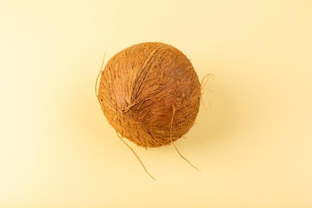 Uma vista superior coco fresco leitoso todo maduro isolado no creme colorido