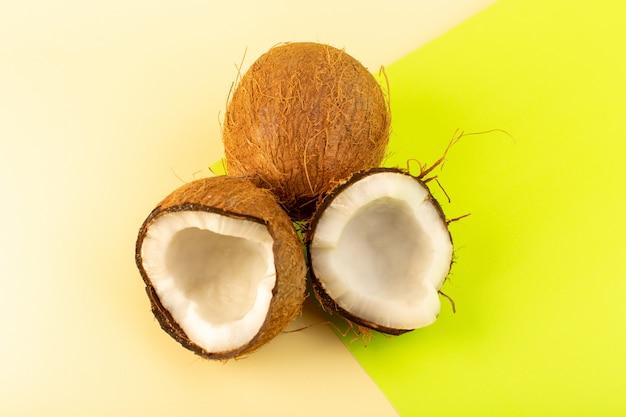 Uma vista superior cocos maduros frescos leitosos inteiros e fatiados isolados no pistache creme colorido