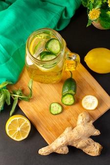 Uma vista superior coquetel de limão bebida fresca e fresca dentro de copo de vidro fatiado e limões inteiros pepinos junto com flores sobre o fundo escuro coquetel de frutas