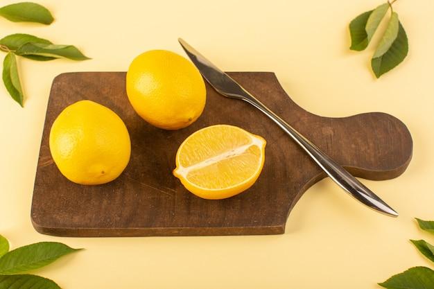 Uma vista superior cortada maduro fresco suculento de limão inteiro junto com faca de prata e folhas verdes na mesa de madeira marrom e laranja cítrica de fundo creme