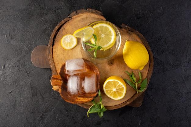 Uma vista superior da água com uma bebida fresca de limão dentro de um copo com cubos de gelo com limões fatiados no fundo escuro