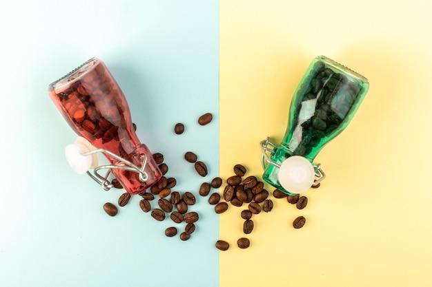 Uma vista superior das sementes de café marrom dentro de potes de vidro colorido na superfície azul-amarela da foto colorida da bebida de sementes de café