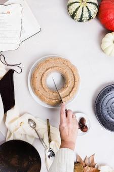 Uma vista superior de alguém cortando um bolo de pumkpin em uma mesa branca com ingredientes e o livro de receitas