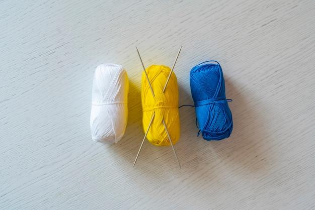 Uma vista superior de alguns rolos de fios com algumas agulhas de tricô inseridas na mesa