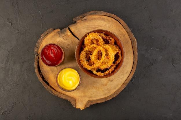 Uma vista superior de anéis de frango frito dentro de um prato marrom com ketchup e mostarda