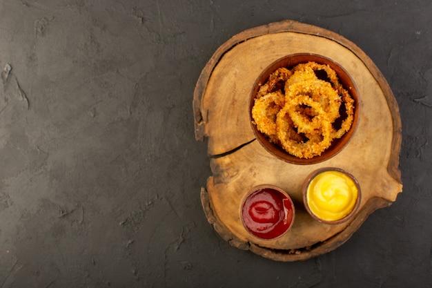 Uma vista superior de anéis de frango frito dentro do prato com ketchup e mostarda