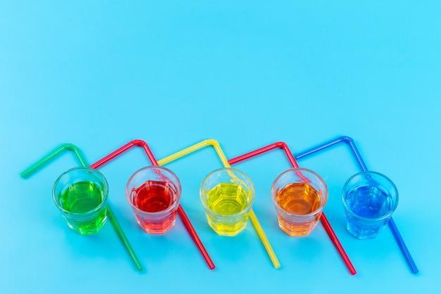 Uma vista superior de bebidas coloridas dentro de copos de plástico com canudos multicoloridos isolados em azul
