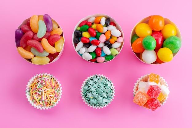Uma vista superior de doces coloridos dentro de diferentes pacotes de papel em uma mesa rosa