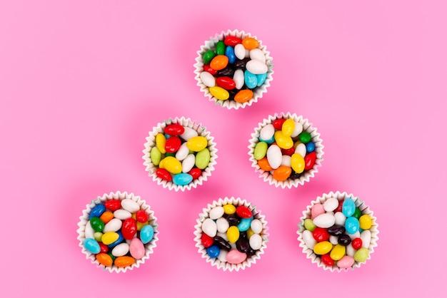 Uma vista superior de doces coloridos dentro de pacotes de papel na cor rosa