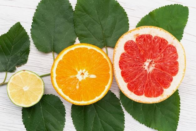 Uma vista superior de frutas cítricas frescas cortadas junto com folhas verdes em cítricos de cor de frutas brancas