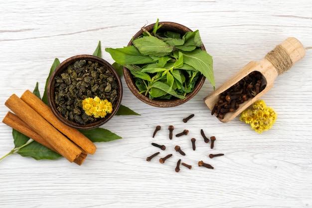 Uma vista superior de hortelã e canela com especiarias em branco, folhas de ingredientes
