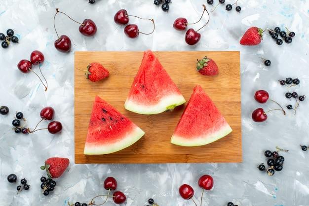 Uma vista superior de melancia fatiada e suave em madeira marrom ao redor de frutas em brilhante