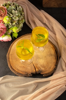 Uma vista superior de óculos com suco de suco de limão dentro de vidros transparentes ao longo de limão e flores na mesa de madeira marrom e cinza