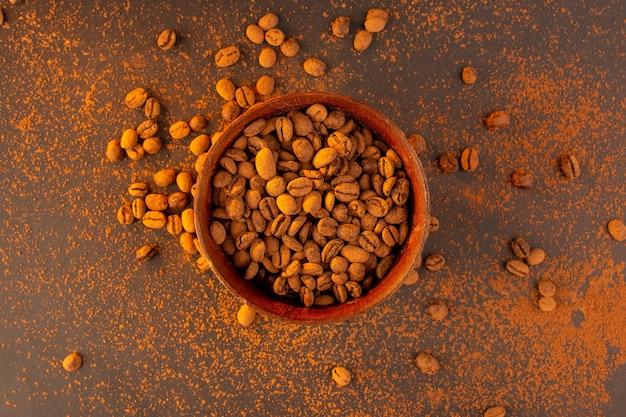 Uma vista superior de sementes de café marrom dentro de um prato marrom na mesa marrom