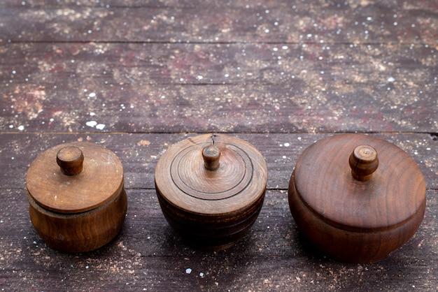 Uma vista superior de tigelas de madeira marrom arredondadas formadas na foto da placa de prato de mesa de madeira marrom