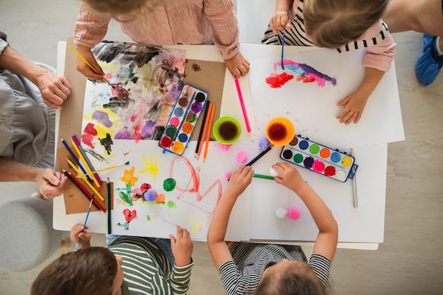Uma vista superior de um grupo de crianças de uma escola maternal pequena com o professor dentro de casa na sala de aula, pintando.
