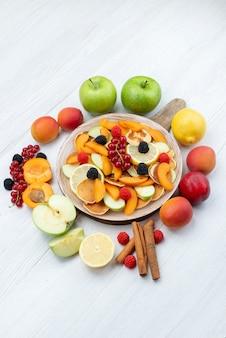 Uma vista superior distante frutas fatiadas frescas coloridas e maduras com canela na mesa de madeira e fundo branco frutas coloridas foto de alimentos